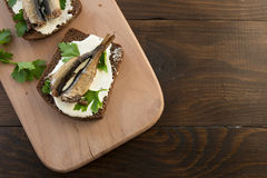 Sandwich with sprats. A tasty sandwich with smoked sprats with white cheese and green parsley on the wooden cutting board Royalty Free Stock Image