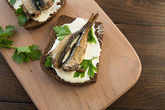 Sandwich with sprats. A tasty sandwich with smoked sprats with white cheese and green parsley on the wooden cutting board Royalty Free Stock Images