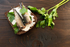 Sandwich with sprats. A tasty sandwich with smoked sprats with white cheese and green parsley on the wooden cutting board Stock Photos