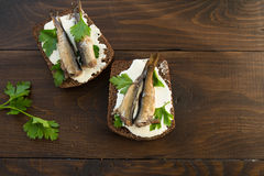 Sandwich with sprats. A tasty sandwich with smoked sprats with white cheese and green parsley on the wooden cutting board Stock Images
