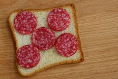 Square piece of bread and sliced sausage salami on a brown table. Sandwich of a square piece of bread and sliced sausage salami on a brown wooden board royalty free stock images
