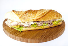 Sandwich. A sandwich stuffed with lettuce, ham and cheese Stock Images