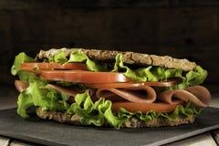 Sandwich sur la table en bois avec des tranches de tomates, de jambon, et de laitue frais photo libre de droits