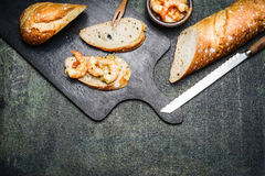 Sandwich or tapas with shrimps on dark rustic background Royalty Free Stock Image