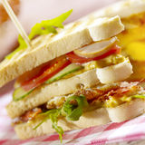 Sandwich with three layers, filled with bacon eggs and lettuce Royalty Free Stock Photo