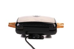 Sandwich toaster with bread slices. Royalty Free Stock Photos