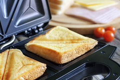Sandwich toaster with toast Stock Photography