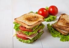 Sandwich, Tomate, Toast, Salat auf weißem hölzernem Hintergrund Lizenzfreie Stockfotos