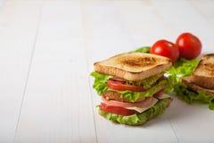 Sandwich, Tomate, Toast, Salat auf weißem hölzernem Hintergrund Stockfotografie