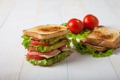 Sandwich, Tomate, Toast, Salat auf weißem hölzernem Hintergrund Lizenzfreies Stockbild