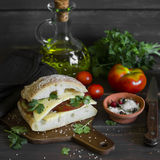 Sandwich with tomato and cheese, served on a cutting Board on dark wooden surface Stock Photo