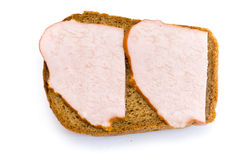 Sandwich top view. A sandwich with two slices of ham on rye bread, white background royalty free stock photo
