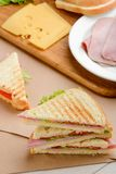 Sandwich triangles and ingredients. On kitchen table. Delicious snack made of toast bread, herbs, vegetables, ham and cheese stock photo