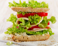 Sandwich with turkey and fresh vegetables on a wooden background Stock Photos