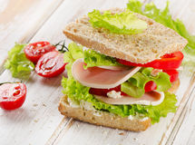 Sandwich with turkey and fresh vegetables on  a wooden table Stock Photo