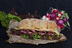 Sandwich van knapperige ciabatta met ham, kaas en slabladeren royalty-vrije stock afbeeldingen