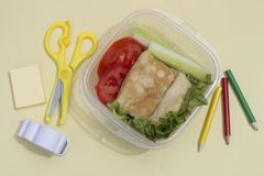 Sandwich with vegetables in a container, school lunch, multicolored pencils and book on a yellow background, top view stock photo