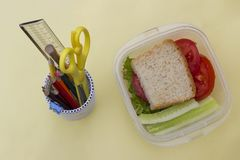 Sandwich with vegetables in a container, school lunch, multicolored pencils and book on a yellow background, top view royalty free stock photography