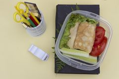 Sandwich with vegetables in a container, school lunch, multicolored pencils and book on a yellow background, top view royalty free stock photos