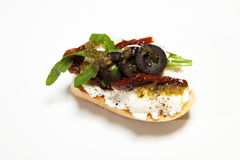 Sandwich with white cheese, dried tomato, olives and arugula on. The white background Stock Photography