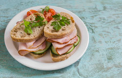 Sandwich with whole grain bread, cucumber and ham on a white plate Stock Photography