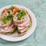 Sandwich with whole grain bread, cucumber and ham on a white plate Stock Photos