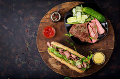 Sandwich of whole wheat bread with roast beef, cucumber and arugula Stock Photos