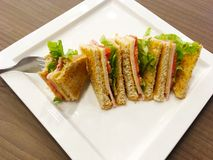 Sandwich wholewheat bread on white plate. Breakfast diet food. Fork pick sandwich wholewheat bread with lettuce, ham and yellow cheese on white plate over wooden Stock Image