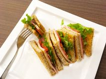 Sandwich wholewheat bread on white plate. Breakfast diet food. Fork pick sandwich wholewheat bread with lettuce, ham and yellow cheese on white plate over wooden Royalty Free Stock Image