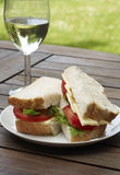 Sandwich and wine picnic. An outdoor tabletop view of a fresh tomato and cheese sandwich on a plate and a glass of white wine Stock Photography