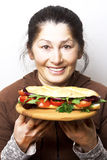 Sandwich. Woman with a sandwich with tomatoes, bell pepper,red onion and arugula stock image
