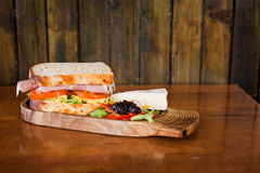 Sandwich on wooden board with brie and salad. Ham, tomato,chicken and lettuce sandwich on a wooden board on a wooden table and wood backdrop Royalty Free Stock Photos