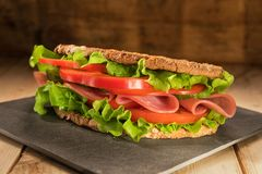 Sandwich on the wooden table with slices of fresh tomatoes, ham, and lettuce stock photos