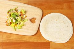 Sandwich wrap ingredients. Sandwich wraps and ingredients on a wooden chopping board stock photography