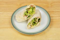 Sandwich wraps on a table. Chicken, bacon and salad sandwich wraps on a plate on a wooden tabletop royalty free stock images