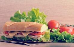Sandwichbaguette met kippenborst, kaas en tomaten stock foto's