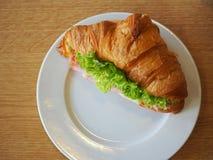 Sandwichcroissant op houten lijst Stock Afbeelding