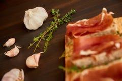 Sandwiche gemacht vom handgemachten Roggenbrot und von dünn gehacktem frischem Speck Frischer grüner Thymian auf einem hölzernen  lizenzfreie stockbilder