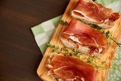 Sandwiche gemacht vom handgemachten Roggenbrot und von dünn gehacktem frischem Speck Frischer grüner Thymian auf einem hölzernen  stockbild
