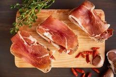 Sandwiche gemacht vom handgemachten Roggenbrot und von dünn gehacktem frischem Speck Frischer grüner Thymian und heißer roter Pfe lizenzfreie stockfotos
