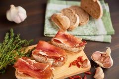 Sandwiche gemacht vom handgemachten Roggenbrot und von dünn gehacktem frischem Speck Frischer grüner Thymian und heißer roter Pfe stockfotos