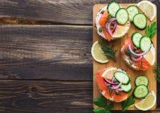 Sandwiche mit geräuchertem Lachs, roter Zwiebel, Kapriolen, Gurke und Zitrone Stockbilder