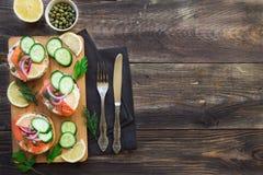 Sandwiche mit geräuchertem Lachs, roter Zwiebel, Kapriolen, Gurke und Zitrone Lizenzfreies Stockfoto