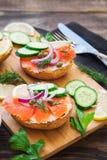 Sandwiche mit geräuchertem Lachs, roter Zwiebel, Kapriolen, Gurke und Zitrone Stockfoto