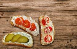 Sandwiche mit Käse, Kirschtomaten und Gurken mit Hüttenkäsepaste auf einem Holztisch stockfotos