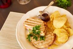Sandwiche mit Käse und Wurst brieten auf dem Grill Eine Platte mit Snäcken von Chips und von Toastbrot Weißer Teller mit den Aper Lizenzfreies Stockbild