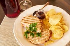 Sandwiche mit Käse und Wurst brieten auf dem Grill Eine Platte mit Snäcken von Chips und von Toastbrot Weißer Teller mit den Aper Lizenzfreie Stockbilder