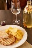 Sandwiche mit Käse und Wurst brieten auf dem Grill Eine Platte mit Snäcken von Chips und von Toastbrot Weißer Teller mit den Aper Stockfoto