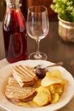 Sandwiche mit Käse und Wurst brieten auf dem Grill Eine Platte mit Snäcken von Chips und von Toastbrot Weißer Teller mit den Aper Lizenzfreie Stockfotos