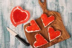 Sandwiche mit rotem Kaviar- und Frischkäse in Form eines Herzens für Valentinstag lizenzfreies stockbild